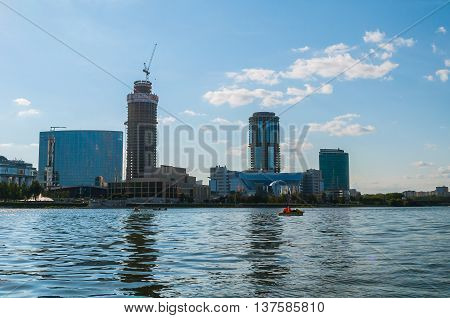 YEKATERINBURG RUSSIA - AUGUST 24 2013. Business center Yekaterinburg City from the water - urban architecture view of modern building on the embankment of Iset river