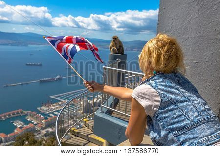 Tourist woman holding an English flag observes one of the famous monkeys of Gibraltar from the top of Gibraltar Rock, in the Upper Rock Natural Reserve.