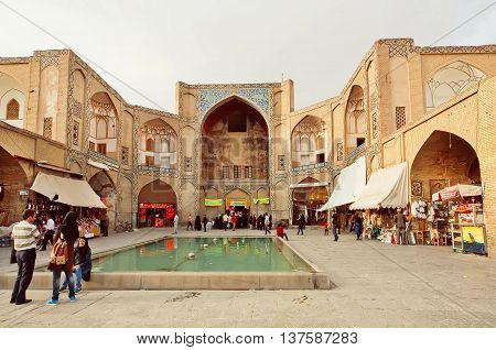 ISFAHAN, IRAN - OCT 16, 2014: People meeting at square near the walls of 17th century bazaar of historical persian city on October 16, 2014. Isfahan is the 3rd largest city of Iran