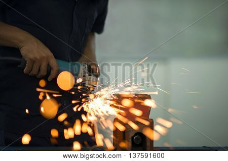 Man grinding steel with grinder. Sparks while grinding iron
