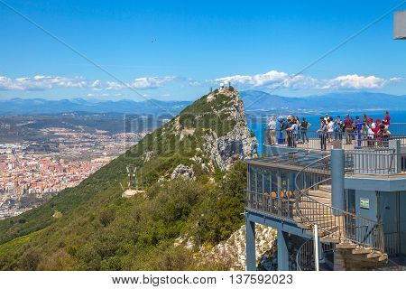 Gibraltar, Europe, United Kingdom - April 24, 2016: Group of tourists observe the spectacular panorama of Gibraltar Town from the top of Gibraltar Rock located on the Upper Rock Natural Reserve.
