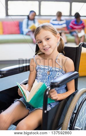 Portrait of smiling disabled school girl reading book in library at school