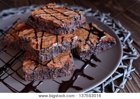 Chocolate brownies on a brown plate and wooden background