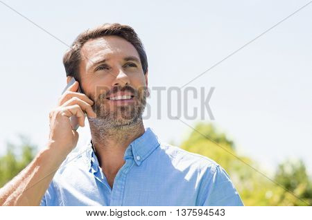 Happy man talking over phone on a bright sunny day and looking up. Smiling mature man using mobile phone outdoor. Portrait of a man in a conversation through mobile phone.
