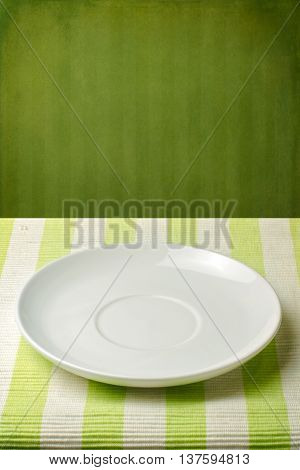 Empty plate on striped tablecloth over green vintage wall