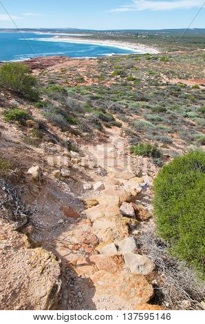Hiking path through the sandstone and bushland at Red Bluff with elevated views over the Indian Ocean waters on the coral coast in Kalbarri, Western Australia.