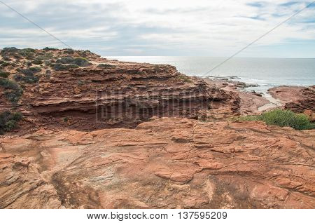Sandstone bluffs with Indian Ocean inlet at Red Bluff beach on the coral coast under an overcast sky in Kalbarri, Western Australia.