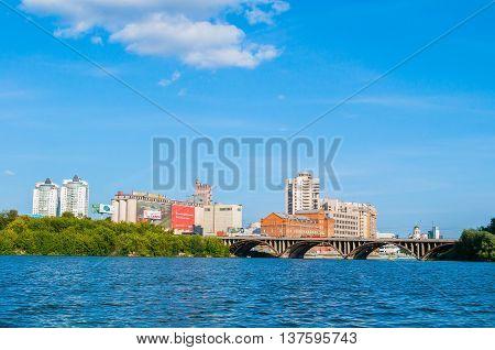 YEKATERINBURG RUSSIA - AUGUST 24 2013.Panoramic view of modern and historic buildings along the embankment and Makarov bridge- the longest bridge across the Iset river in Yekaterinburg Russia