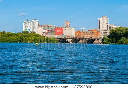 YEKATERINBURG RUSSIA - AUGUST 24  2013.Panorama of modern and historic buildings along the embankment and Makarov bridge- the longest bridge across the Iset river in Yekaterinburg Russia