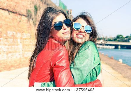 Young women hugging at pier before leaving - Cheerful trendy girls embracing outdoor - Love and friendship concept