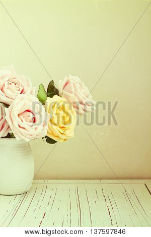 Vintage background with roses bouquet on white table
