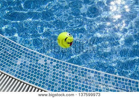 Swimming pool and small ball with protruding and winking face