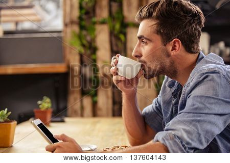Profile view of hipster man using tablet at cafe while sipping cup of coffee