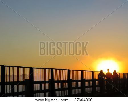 A group of people walking into the sunset