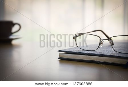 Glasses And A Book On The Desk Wood
