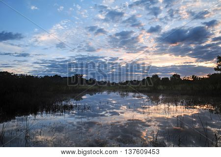 Sunrise on the lake in the forest with clouds. Morning landscape.