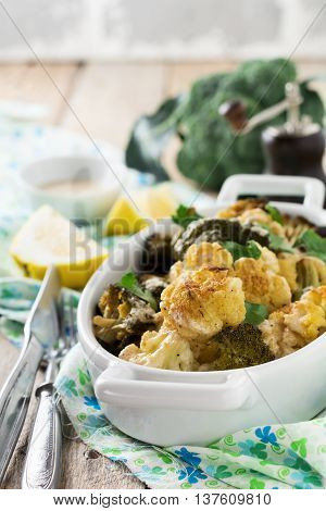 Baked cauliflower and broccoli with a sauce of tahini in a white ceramic plate on old wooden background. Selective focus.