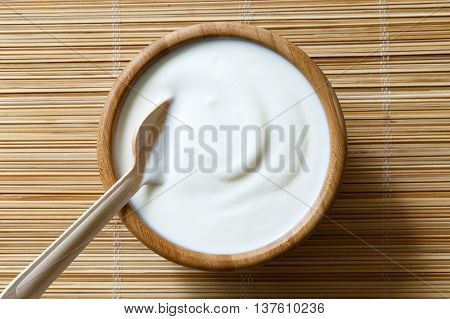 Wooden Bowl Of White Yoghurt With Wooden Spoon Inside On Bamboo Matt From Above .