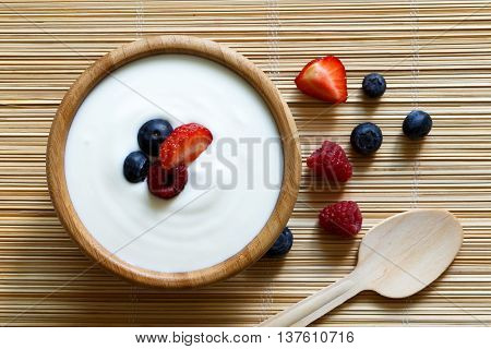 Wooden Bowl Of White Yoghurt On Bamboo Matt From Above With Wooden Spoon. Next To Berries.