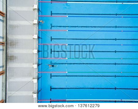 Captured top view of swimming pool and 2 swimmer