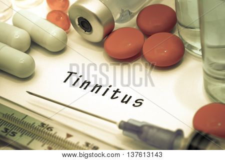 Tinnitus - diagnosis written on a white piece of paper. Syringe and vaccine with drugs.