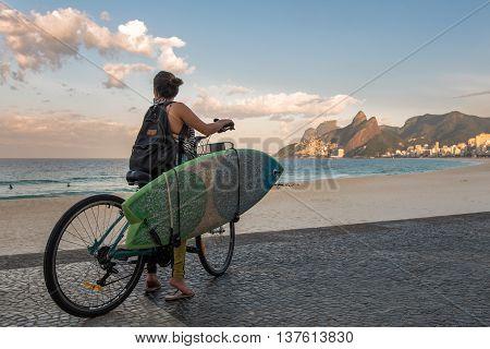 Rio de Janeiro, Brazil - July 7, 2016: Female surfer on a bike looking at the ocean in Ipanema beach.