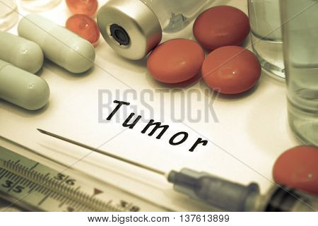Tumor - diagnosis written on a white piece of paper. Syringe and vaccine with drugs.