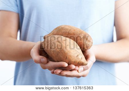 Close Up Of Woman Holding Sweet Potato