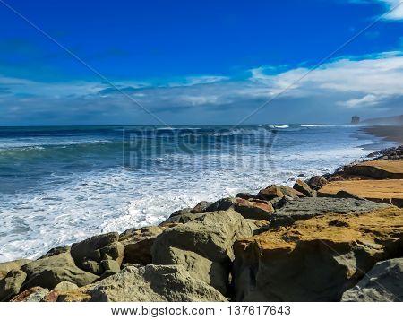 Landscape of coastline with waves breaking in front of rocks