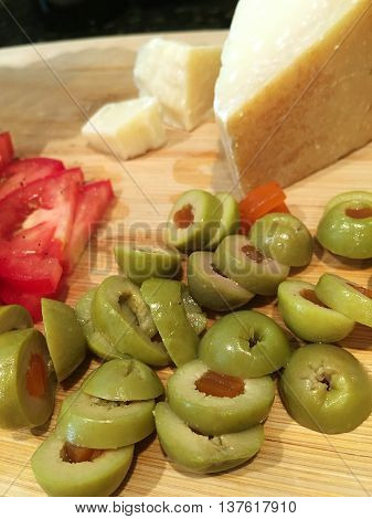 Tomatoes, olives and Parmesan cheese on a cutting board.
