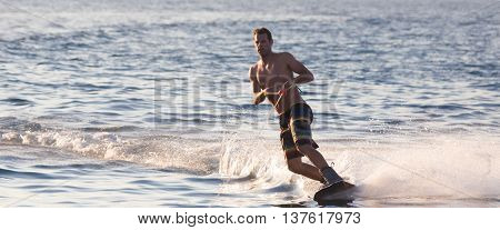 Wakeboarder in colorful shorts riding in sunset.