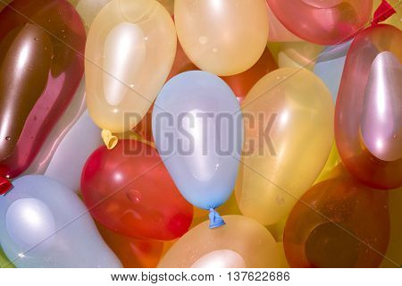 Colorful water balloons on pool seen from top view angle summertime fun concept.