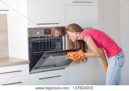 A Girl Prepares Food In The Oven.
