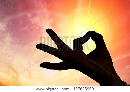 Esotericism and meditation concept. Silhouette of hand in sunset.