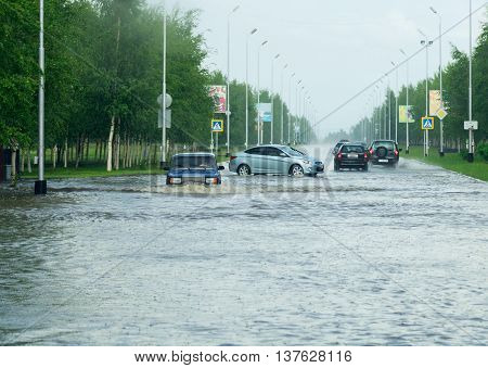 Cars driving on the road in a heavy downpour.