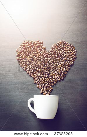 Heart consist from coffee beans. Coffee roasted beans on a shape like a heart and coffee cup. Rustic background. Energy.