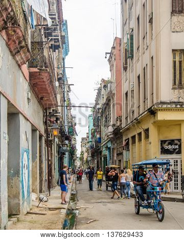 HAVANA - CUBA JUNE 17, 2016: O'Reilly is a busy, narrow street in the historic La Habana Vieja neighborhood where people use a pedicab for transportation if they are not walking.
