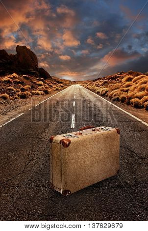 Vintage suitcase in the middle of a grungy asphalt road leading through desert landscape