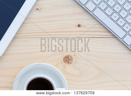 Top View of Wood Table with Computer Keyboard Tablet PC and White Coffee Cup on fresh batten texture