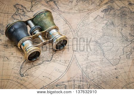 Pair of old binoculars on a vintage map