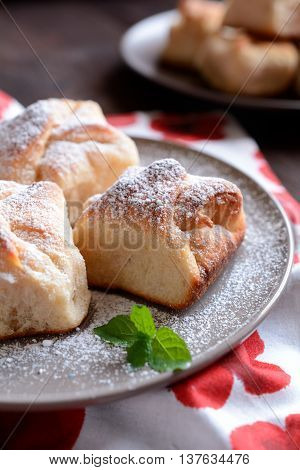 Baked yeast dumpling with curd filling on a wooden background