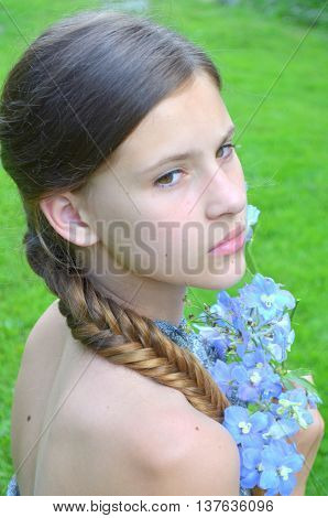 Hairstyle with long hair - a girl with a bouquet of blue delphinium
