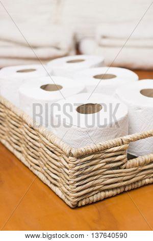 Toilet paper rolls on wicker basket in home