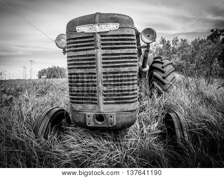 SASKATCHEWAN, CANADA - JUNE 30: An abandoned tractor on June 30, 2016 in field in Saskatchewan, Canada. Saskatchewan is a major agricultural producer in Canada.