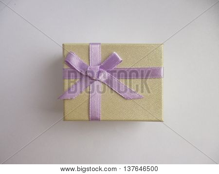 Little gift box with purple silky bow. Top view