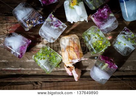 Frozen Flowers In Ice Cubes On Rustic Wooden Background