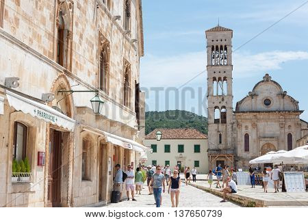 HVAR CROATIA - JUNE 20 2014: Hvar town main square with lots of tourists in front of the St Stephen Cathedral in Hvar Croatia