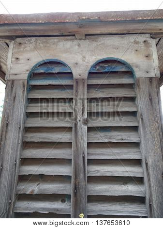 Vertical upward composition of rustic wooden shutters with rich accents of peeling Mediterranean blue paint and rusted metal