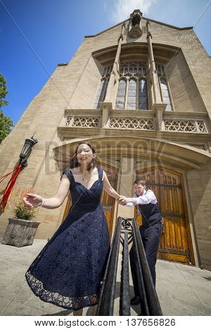 Funny bride pretending to runaway from groom on wedding day
