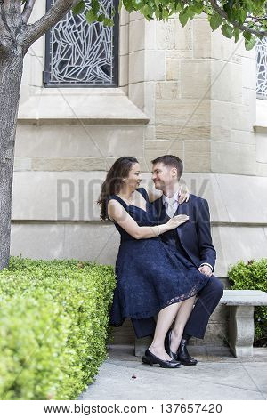 Young romantic couple engaged to be married outside a church